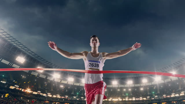 male track and field runner crosses finishing line - atletico video stock e b–roll