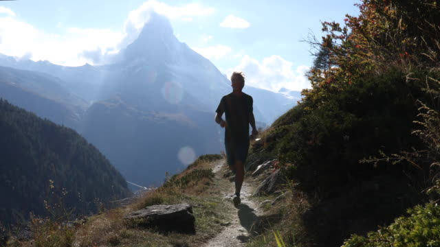 stockvideo's en b-roll-footage met mannelijke trail runner volgt alpine trail, matterhorn verre - gymbroek