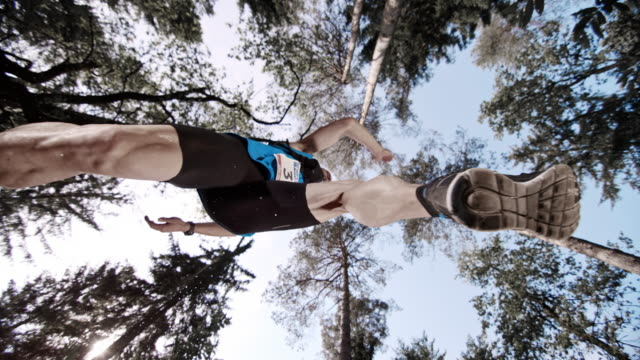 SLO MO Male trail runner jumping across a path in the forest
