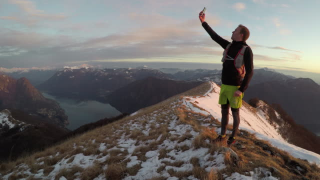 Male trail runner searches for cell service on snowy mountain ridge above lake at sunset