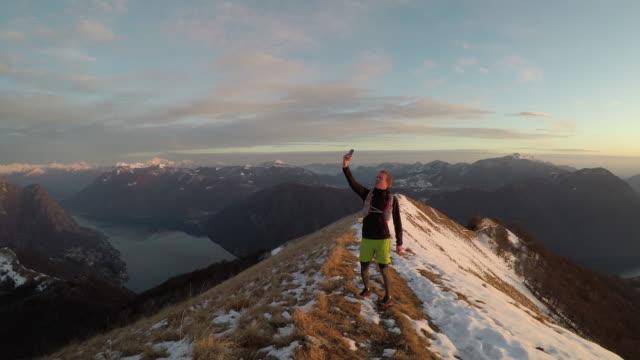 vídeos y material grabado en eventos de stock de corredor de trail hombre busca servicio de celular en cresta de montaña cubierto de nieve sobre el lago al atardecer - top