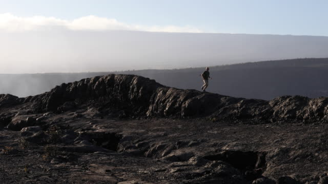 male trail runner sprints across volcanic plateau - volcano stock videos & royalty-free footage