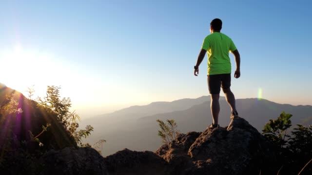 Male trail runner summit on the mountain peak