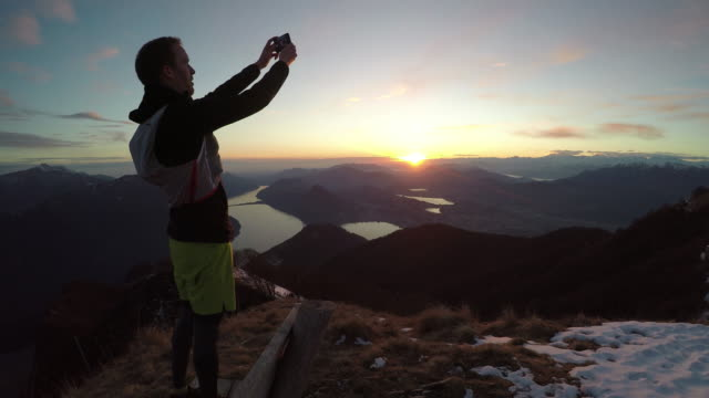 Male trail runner takes selfie on snowy mountain above lake at sunset