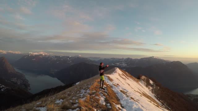 Male trail runner takes selfie on snowy mountain ridge above lake at sunset