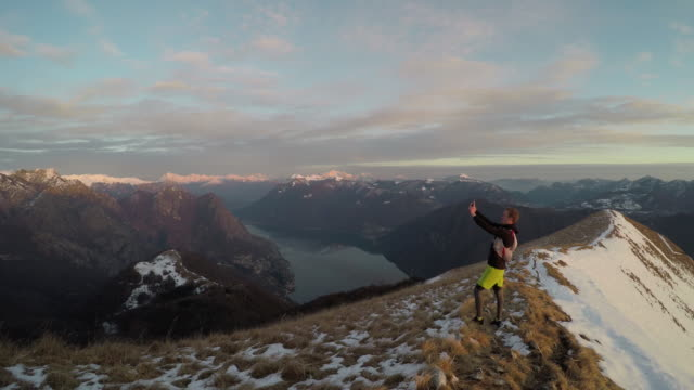 Male trail runner takes selfie on snowy mountain ridge above lake at sunset