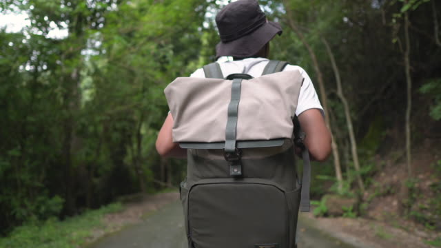 male traveler walking on rural road with his backpack - one man only stock videos & royalty-free footage