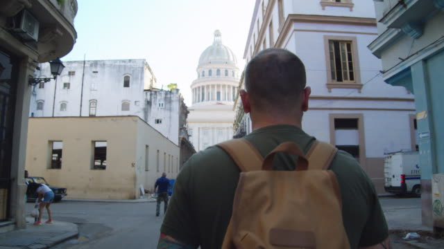 male traveler walking up a street leading to the cuban national capitol building in havana, cuba - cuba stock videos & royalty-free footage