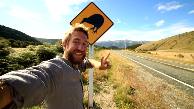 male traveling takes selfie portrait with kiwi sign, new zealand - road warning sign stock videos & royalty-free footage