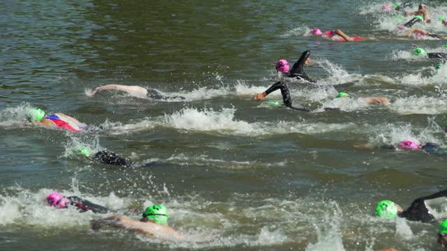 vídeos de stock e filmes b-roll de pan male triathlete swimmers at race in a canal - touca de natação