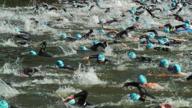 vídeos y material grabado en eventos de stock de male triathlete swimmers at race in a canal - triatlón