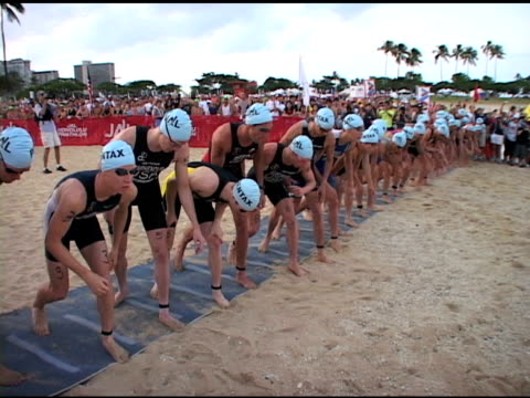male triathletes into water at the start of 2009 honolulu triathlon male triathletes into water at start honolulu on january 01 2010 - salmini stock videos and b-roll footage