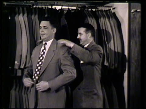male trying on suit jacket in store w/ help from male sales person ms salesman offering hat for another male customer to try on vs associates showing... - salesman stock videos & royalty-free footage