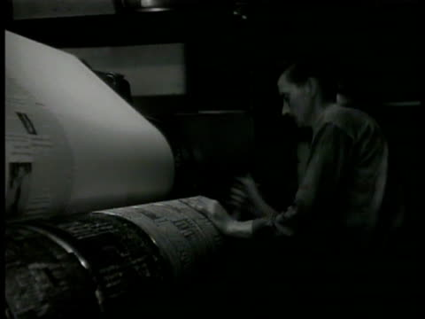 newspapers male typing on mergenthaler linotype keyboard male tightening printing press roll ha td folded newspapers passing on conveyor men reading... - linotype stock videos and b-roll footage