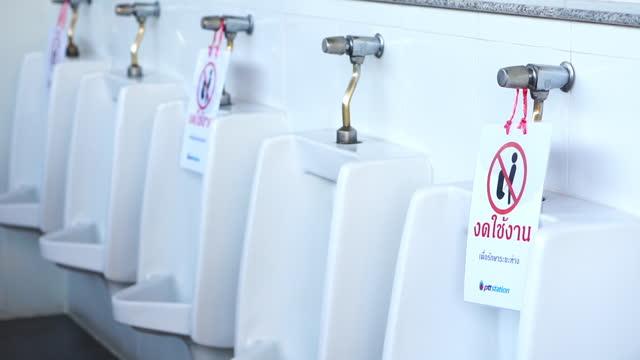 男性の尿 コロナウイルス病の感染を避けるために洗面所の便器の社会的距離 - 小便器点の映像素材/bロール