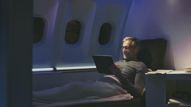 vidéos et rushes de mâle utilisant la tablette numérique dans l'avion - voyage d'affaires