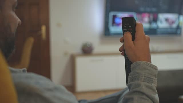maschio che utilizza il microfono del telecomando per scegliere il programma tv a casa - remote control video stock e b–roll