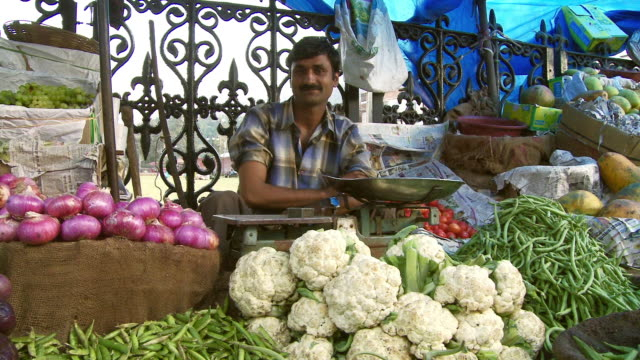 male vendor selling vegetables cauliflower, potatoes, peas outdoors   - retail occupation stock videos and b-roll footage