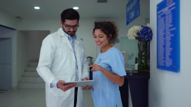 vídeos y material grabado en eventos de stock de veterinario masculino hablando con asistente ambos mirando la tableta en el veterinario - ayudante