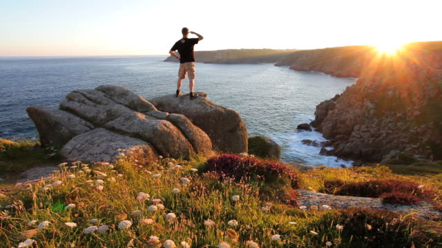 Male viewing the setting sun Treen Cliffs, Porthcurno, Cornwall, UK