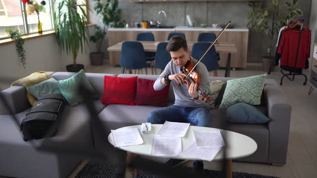 male violinist cleaning his violin on sofa at home - sketch comedy stock videos & royalty-free footage