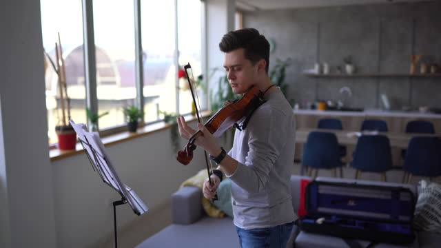 male violinist rehearsing music piece in living room - sketch comedy stock videos & royalty-free footage