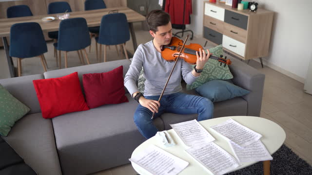 male violinist rehearsing music piece on sofa at home - sketch comedy stock videos & royalty-free footage