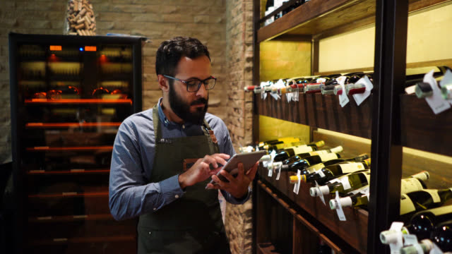 male waiter doing an inventory of the wine bottles on rack at a restaurant using a tablet - wine bar stock videos & royalty-free footage