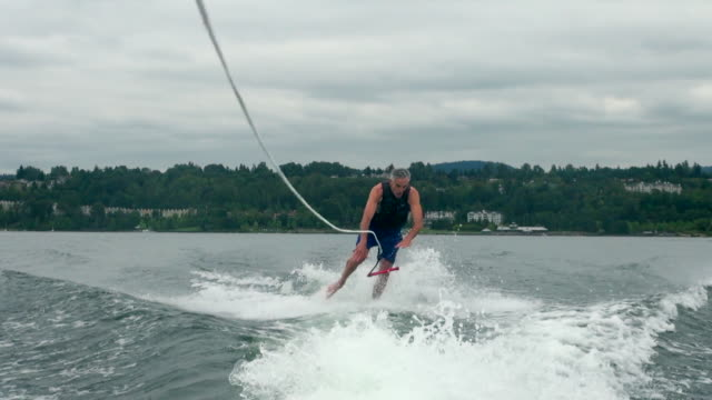 male wake skater losing balance and falling to water - wassersport stock-videos und b-roll-filmmaterial