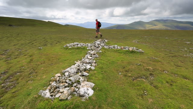 Male walker passing the White Cross memorial on Blencathra fell, Lake District National Park, Cumbria, England, UK