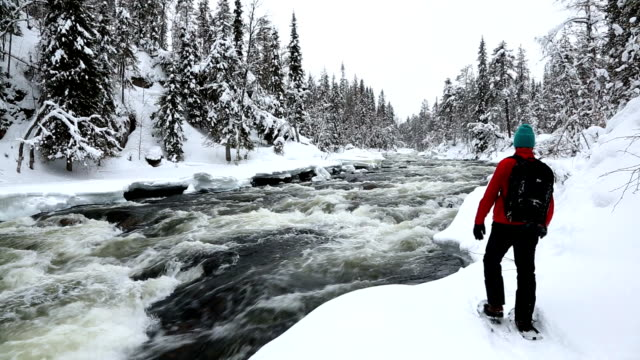 Male walker wearing snow shoes river bank Oulanka Nat Pk Lapland