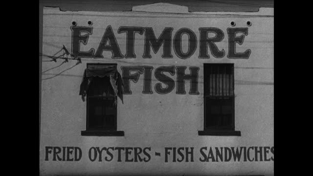 vidéos et rushes de male walking out of roadside restaurant w/ car parked fg. male in freezer w/ boxes of fish. vs signs: 'fish & chips', 'fish sandwich 15 cents',... - bord de route