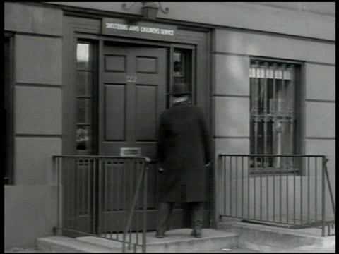 vidéos et rushes de male walking toward foundling home. door sign 'child placing & adoption committee' vs couples waiting in reception area. orphan, foundling, foster... - famille d'accueil