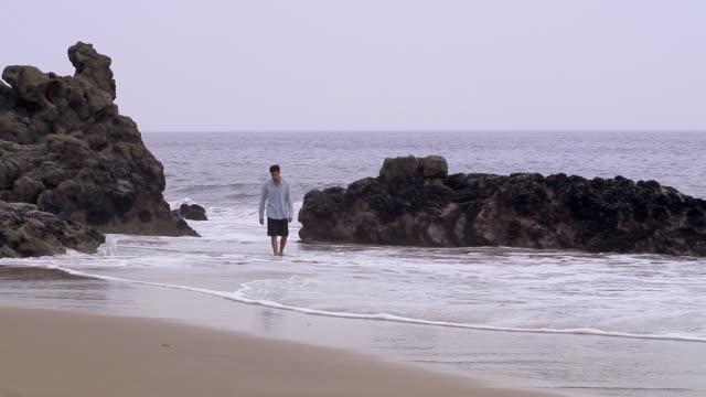 W/S Male walks along beach.