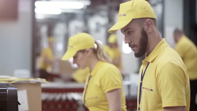 vidéos et rushes de magasinier mâle, saisie de données des documents qu'il tient dans l'ordinateur - service postal