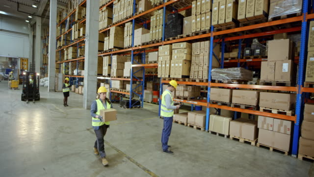 cs male warehouse supervisor working in the warehouse with other employees - warehouse stock videos & royalty-free footage