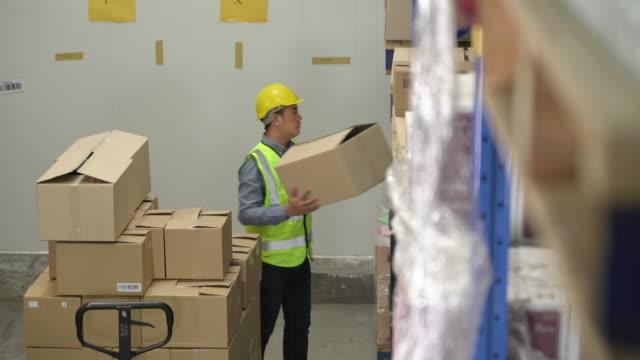 männlicher lagerarbeiter, der die boxen ins regal stellt - hubwagen stock-videos und b-roll-filmmaterial