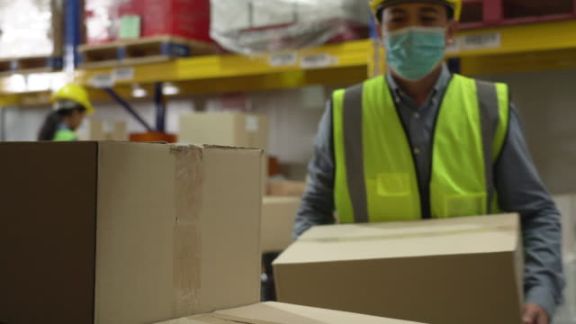 a male warehouse worker stacking the cardboard boxes in storage room - loading stock videos & royalty-free footage