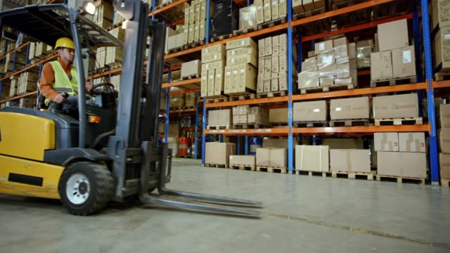 cs male warehouse worker using a forklift to take a pallet off the rack - forklift stock videos & royalty-free footage