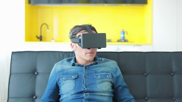 male wearing a virtual reality headset at home. - watch timepiece stock videos and b-roll footage