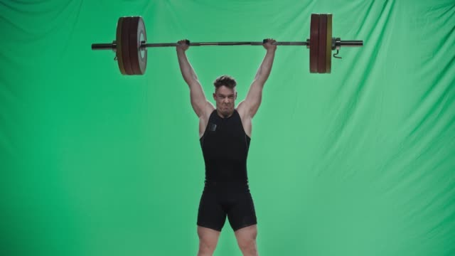 male weightlifter in black outfit performing the clean and jerk lift - weight training stock videos & royalty-free footage