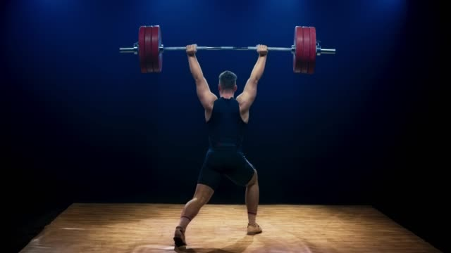 ld male weightlifter lifting a barbell at a competition - picking up stock videos & royalty-free footage