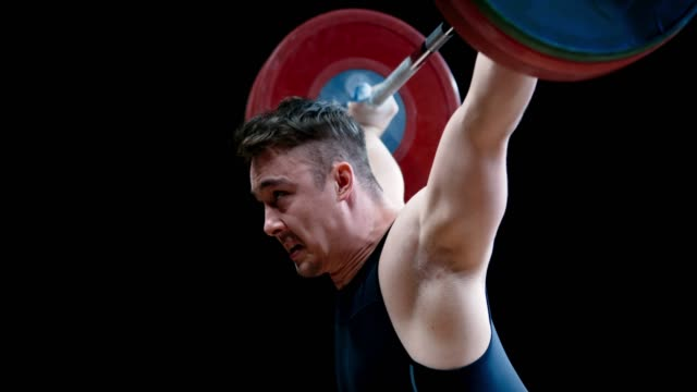 slo mo male weightlifter lifting the barbell over his head - weight training stock videos & royalty-free footage