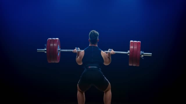 male weightlifter lifting the barbell with the clean and jerk lift at a competition - sollevamento pesi video stock e b–roll