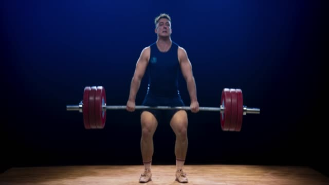 male weightlifter performing clean and jerk at a competition - weight training stock videos & royalty-free footage