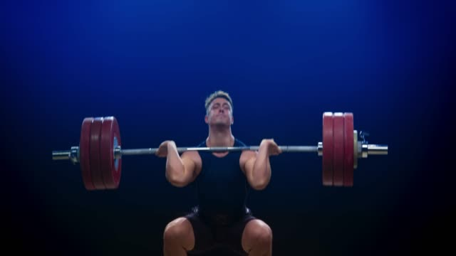 male weightlifter performing the clean and jerk at a competition - weights stock videos & royalty-free footage
