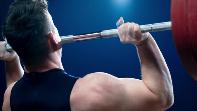 彼の胸から頭上にバーベルを上げる slo mo tu オス重量挙げ - ウエイトトレーニング点の映像素材/bロール