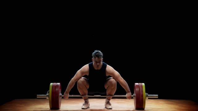 ld male weightlifter raising the barbell using the snatch lift at a competition - weight training stock videos & royalty-free footage