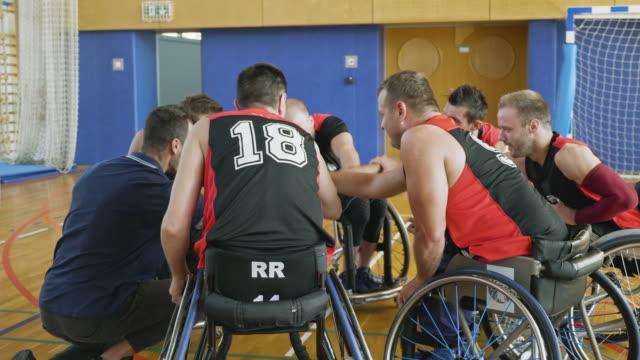 vidéos et rushes de joueurs masculins de basket-ball en fauteuil roulant gesturing solidarité - équipe sportive