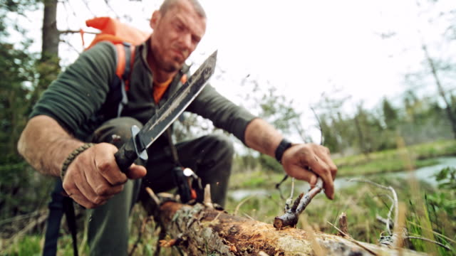 slo mo male wilderness survival expert cutting small branches with his knife - survival stock videos & royalty-free footage
